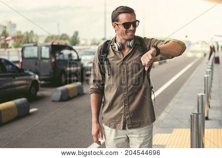 What time. Cheerful young guy in sunglasses is looking at his watch. He is standing with backpack and headphones near road and expressing happiness. Copy space in the left side