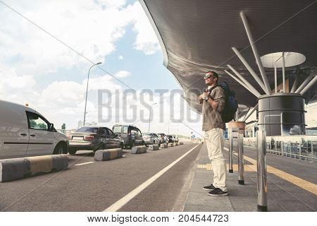 Positive stylish adult tourist in sunglasses is looking aside with smile. He is standing near road with backpack. Copy space in the left side