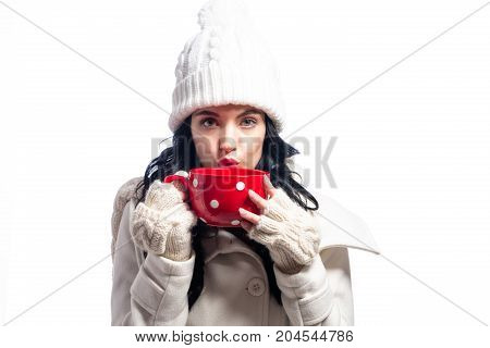 Happy young woman in winter clothes drinking coffee