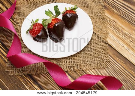 Valentine's Day. Fresh strawberries dipped in dark chocolate and heart on wooden background.