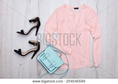 Pink Blouse With A Tag, Black Shoes, Mint Bag. Fashionable Concept. Wooden Background