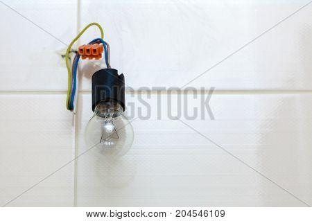 Renovation objects electricity details concept. Small bulb hanging on bare wires white tiles in background.