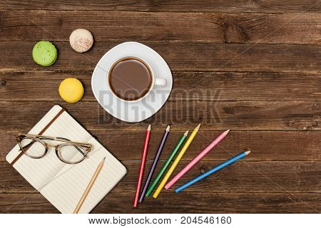 Coffee Mug, Macaroons, Colored Pencils And A Notepad With Glasses On A Wooden Background. Top View,