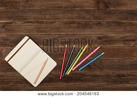 Colored Pencils And A Notepad  On A Wooden Background. Copy Space