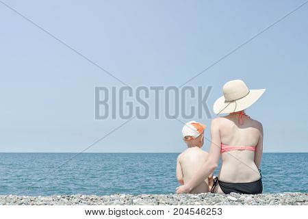 Mom And Son Sitting On The Beach And Admire The Sea. View From The Back