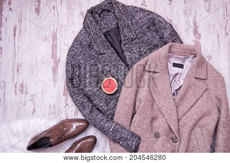 Two Woolen Coat, Brown Patent Leather Shoes On A White Fur, Half A Grapefruit, A Wooden Background.