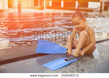 Cute girl with flippers in swimming pool at tropical beach. Toned