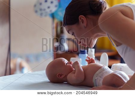 Mom With Cute Smile Takes Care Of Her Newborn Boy On Baby Changing Table