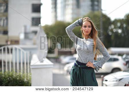 Pretty woman on a street in autumn fashion cloth windy hair looking at the corner urban background
