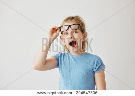 Beautiful little blonde miss with big blue eyes and light hair silly posing with widely opened mouth and raising her glasses with hand