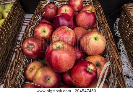Fresh red ripe large apples in a wicker basket on the market counter. Autumn nature concept.