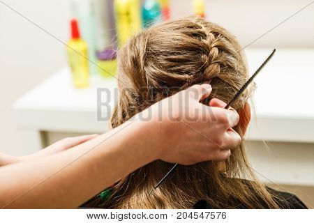 Kids hairstyles and haircare concept. Blonde toddler girl getting her braided hairstyle done at hairdresser