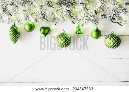 White Wooden Background With Copy Space. Christmas Banner With Green Christmas Decoration Like Balls, Hearts And Bells. Fir Branches With Fairy Lights.