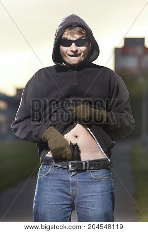 Armed man showing his pistol behind the waist