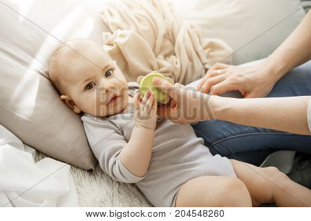 Close up portrait of cute little baby girl looking at camera while playing toys with her young beautiful mother. Family, lifestyle and maternity concept