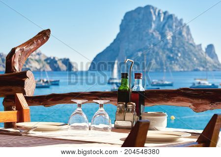 Outdoors restaurant at Cala d'Hort beach with a fantastic view of the mysterious island of Es Vedra. Ibiza Island Balearic Islands. Spain