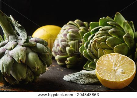 Baby Ripping Organic Artichokes In The Rustic Wooden Board With