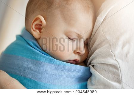 Close up of innocent little child, sleeping on mother hands in blue baby slim. Quite and relaxing scene.