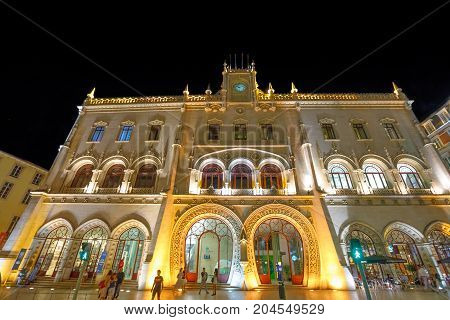 Lisbon, Portugal - August 24, 2017: people at entrance of Rossio Railway Station illuminated at night in Rossio Square, Lisbon downtown. Manueline facade architecture backgroung. Urban night scene.