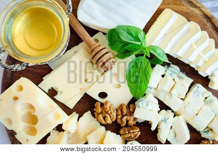 Cheese platter: Parmesan cheddar gouda gorgonzola brie and other with walnuts and honey on wooden board on white background. Tasty appetizers with different kind of cheese. Top view.