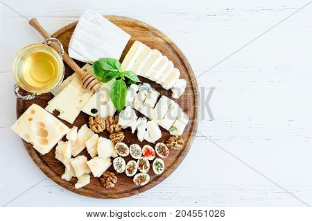 Cheese platter: Parmesan cheddar gouda gorgonzola brie and other with walnuts and honey on wooden board on white background. Tasty appetizers with different kind of cheese. Top view. Copy space.