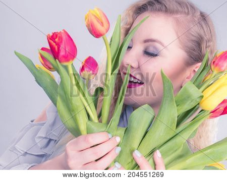 International womens day eight march. Beautiful portrait of pretty woman blonde hair with red yellow tulips fashion make up. Mothers day. On grey