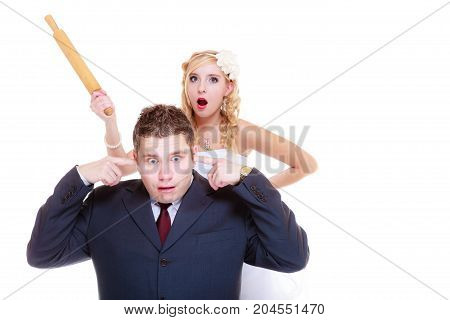 Relationship problems and troubles concept. Groom and bride having quarrel argument woman holding rolling pin