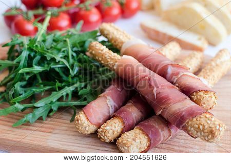 Grissini bread sticks with Prosciutto ham and arugula with tomatoes on wooden board. Delicious appetizer snack on party or picnic time. Chopping board with meat. Italian style.