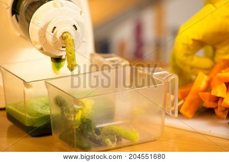 Woman hands adding different vegetables red and green in juicer maker. Housewife in kitchen making raw juice preparing nutritious vitamin packed drink. Healthy eating vegetarian food dieting.