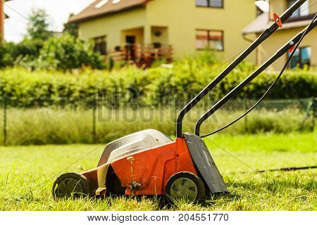 Gardening garden service. Old lawn mower cutting green grass in backyard. Mowing field with lawnmower in sunny day.