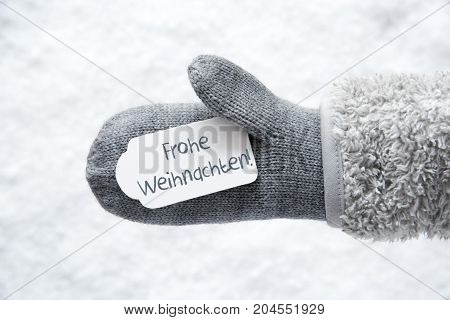 Wool Glove With Label With German Text Frohe Weihnachten Means Merry Christmas. White Snow Background.