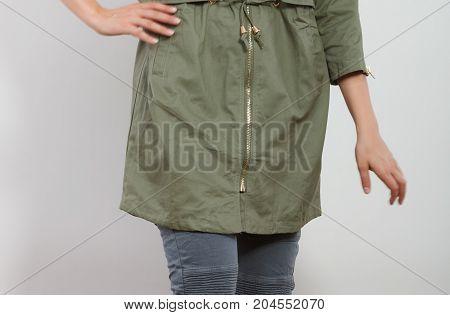 Closeup of woman girl in dark green khaki coat and posing in studio. Winter autumn fall fashion.