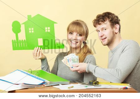 Home real estate credit mortgage concept. Couple with house and money. Young man and woman counting banknotes and holding cartboard cutout.