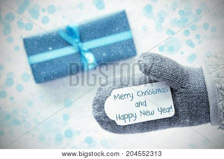 Glove With Label With English Text Merry Christmas And Happy New Year. Turquoise Gift Or Present On Snow In Background. Seasonal Greeting Card With Snowflakes And Bokeh Effect