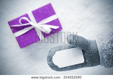 Glove With Label Copy Space For Advertisement. Purple Gift Or Present On Snow In Background. Seasonal Greeting Card With Snowflakes.