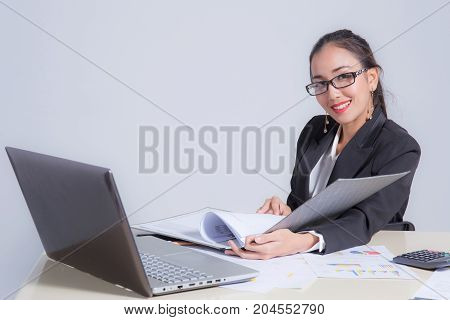 Businesswoman sitting at desk in office. He looks at the camera and smiling.