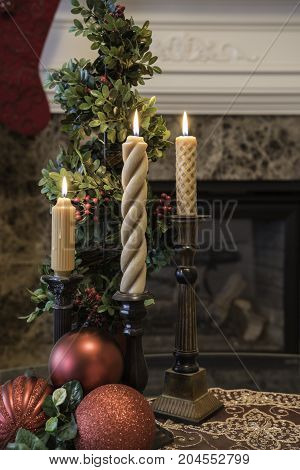 Christmas living room decorations in front of the fireplace with candles and red ball ornaments on the coffee table and a stocking hung at the mantle