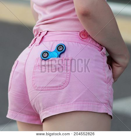 Blue Metal Popular Fidget Spinner In The Back Pocket Of Pink Jeans Shorts, Anxiety Relief Toy, Anti