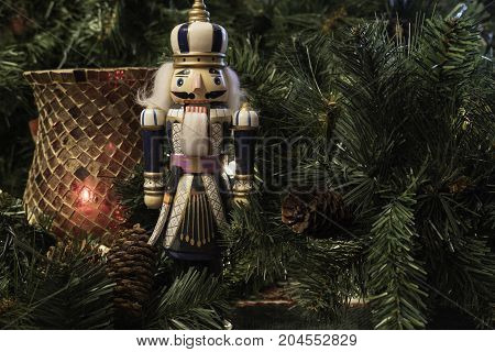 Christmas decoration background with red candle holder and nutcracker surrounded by greenery