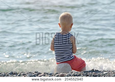 Boy In Striped T-shirt Sitting On The Beach. Back View