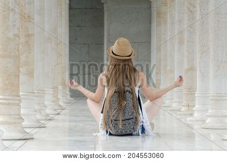 Girl In A Hat With A Backpack Sitting In The Lotus Position Among The Marble Columns. Back View