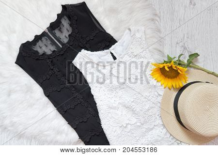 Black And White Lace Dresses, Hat And Sunflower On White Fur. Fashionable Concept, Top View
