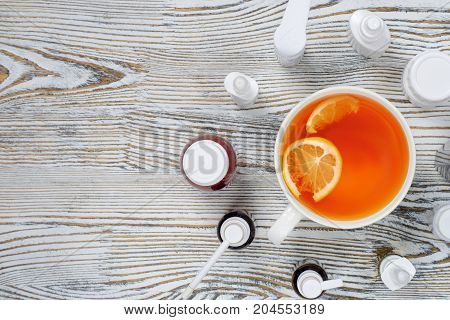 tea with lemon and pills medicine on a wooden background