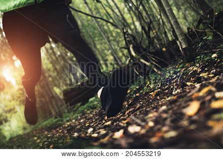 Close-up Photo Of Fast Running Runner On Rough Terrain In Forest. Deliberately Blurred Legs Of Runni