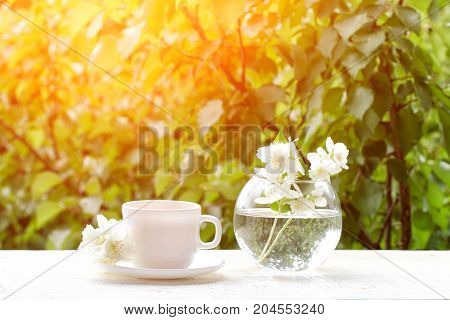 White Mug Of Tea And A Vase With Jasmine On A Wooden Table, Greens On The Background, Sunlight