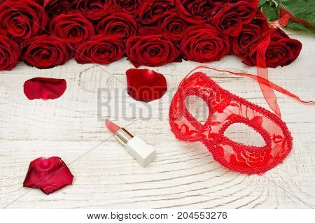 Red Carnival Mask And Lipstick On A Wooden Table, Scarlet Roses On A Background