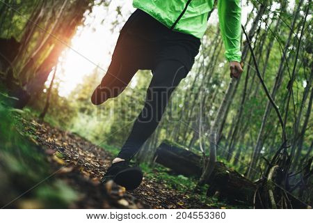 Athlete's Feet In Sportwear And Sneakers Fast Running On Rough Terrain In The Forest. Exercise Outdo