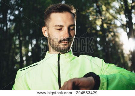 Bearded Athlete With Wireless Bluetooth Headphones Is Studying The Result Of Training And Running On