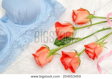 Orange Roses And Blue Bodice With Lace On White Fur. Fashionable Concept. Top View, Close-up