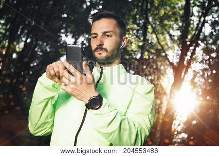 Serious Bearded Sportsmen With Electronic Gadgets Looks At Smartphone And Counts Up Spent Calories A